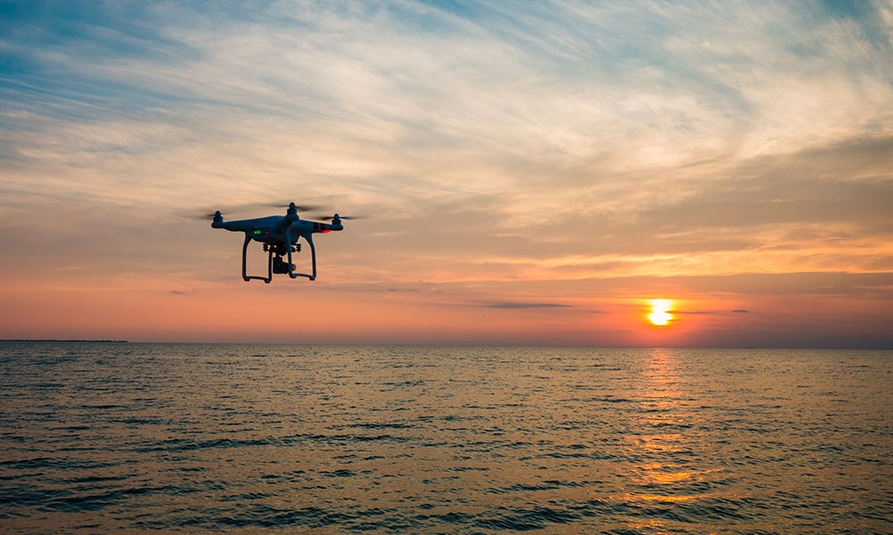 A drone flying above water as the sun sets in the background